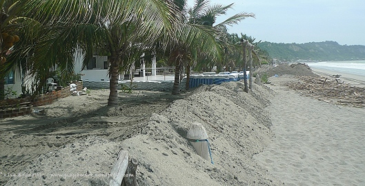Between high tides, people scrambled to place sand barriers to buffer the waves.