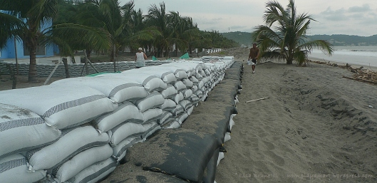 One wonders if a fortified wall of sandbags will hold back the high waves.